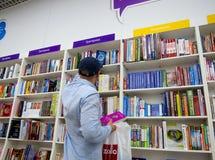 A man chooses books in a bookstore. Voronezh, Russia - June 11, 2017: A man chooses books in a bookstore Stock Photo