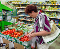 Voronezh, Russia - June 20, 2013, Mature woman chooses tomato in supermarket royalty free stock photo