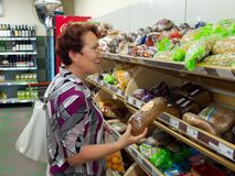 A woman chooses bread from a store Royalty Free Stock Photo