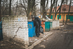 Voronezh, Russia - March 23, 2017: Old homeless man rummages in the dustbin in Voronezh trash.  Stock Photography