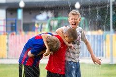 Voronezh, Russland: Am 17. Juni 2013 Jungen unter den Wasserstrahlen im Park an einem heißen sonnigen Tag Freude, Spaß lizenzfreies stockfoto