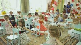 VORONOVO, BIELORRÚSSIA - 27 DE MAIO DE 2017: Crianças encantadores e elegantes no partido de graduação no jardim de infância Danç video estoque