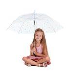 Vorschülerkind mit Regenschirm Reizend Mädchen, das mit dem Regenschirm lokalisiert auf einem weißen Hintergrund sitzt Kindergart lizenzfreies stockfoto