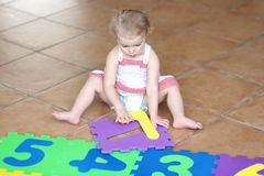 Vorschülermädchen, das mit den Puzzlespielen lernen Zahlen spielt Stockbilder