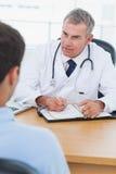 Vorschreibende Droge ernsten Doktors zu seinem Patienten Stockbilder