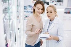 Vorschreibende Drogen des aufmerksamen weiblichen Apothekers lizenzfreie stockbilder