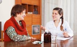vorschreibende Medikation Doktors, zum der Frau zu reifen Lizenzfreie Stockfotos