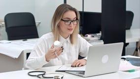 Vorschreibende Medizin weiblichen Medizindoktors unter Verwendung des Laptops lizenzfreie stockbilder