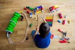 Vorschulkind, spielend mit dem Abakus und anderen Spielwaren und an sitzen Lizenzfreie Stockfotos