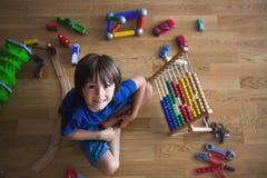 Vorschulkind, spielend mit dem Abakus und anderen Spielwaren und an sitzen Stockfotografie