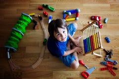 Vorschulkind, spielend mit dem Abakus und anderen Spielwaren und an sitzen Stockfotos