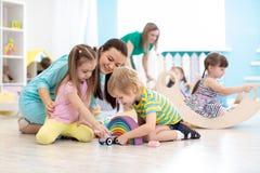 Vorschulkinder, die mit Lehrer im Kindergarten spielen stockfoto