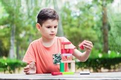 Vorschulkindergestalt ein Turm von bunten hölzernen Bausteinen Stockbild