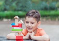 Vorschulkindergestalt ein Turm von bunten hölzernen Bausteinen Lizenzfreie Stockbilder