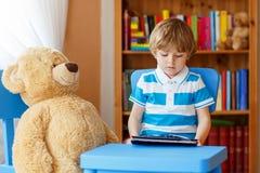 Vorschulkinderjunge, der mit Tablet-Computer in seinem Raum an ho spielt Lizenzfreie Stockfotografie