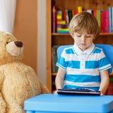 Vorschulkinderjunge, der mit Tablet-Computer in seinem Raum an ho spielt Stockfotografie