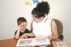 Vorschulkursteilnehmer und Lehrer, die ein Buch liest Stockfotografie
