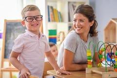 Vorschullehrer mit dem intelligenten Jungen, der mit bunten didaktischen Spielwaren am Kindergarten spielt lizenzfreies stockbild