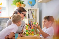 Vorschullehrer mit den Kindern, die mit bunten didaktischen Spielwaren am Kindergarten spielen lizenzfreie stockfotografie
