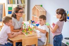 Vorschullehrer mit den Kindern, die mit bunten didaktischen Spielwaren am Kindergarten spielen lizenzfreies stockfoto
