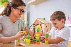 Vorschullehrer mit den Kindern, die mit bunten didaktischen Spielwaren am Kindergarten spielen lizenzfreie stockfotos