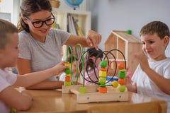 Vorschullehrer mit den Kindern, die mit bunten didaktischen Spielwaren am Kindergarten spielen stockfotografie