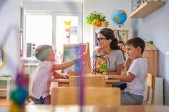 Vorschullehrer mit den Kindern, die mit bunten didaktischen Spielwaren am Kindergarten spielen stockbilder