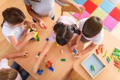 Vorschullehrer mit den Kindern, die mit bunten hölzernen didaktischen Spielwaren am Kindergarten spielen lizenzfreie stockfotografie