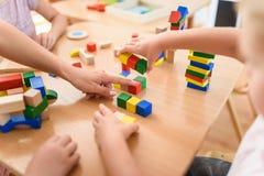 Vorschullehrer mit den Kindern, die mit bunten hölzernen didaktischen Spielwaren am Kindergarten spielen lizenzfreie stockfotos