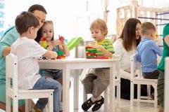 Vorschullehrer mit den Kindern, die mit bunten hölzernen pädagogischen Spielwaren am Kindergarten spielen stockfoto