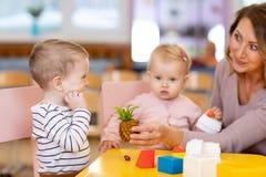 Vorschullehrer mit den Kindern, die mit bunten Spielwaren am Kindergarten spielen stockfoto