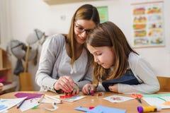 Vorschullehrer mit Kind am Kindergarten - kreativer Art Class lizenzfreies stockbild
