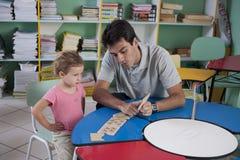 Vorschullehrer und Kind im Klassenzimmer lizenzfreie stockfotos