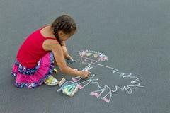 Vorschulmädchen, das eine Kreide auf Asphalt zeichnet Stockfotografie