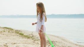 Vorschulmädchen mit Tänzen ein gymnastisches Band auf einem sandigen Strand Sommer, D?mmerung stock footage