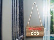 Vorsicht, bissiger Hund auf hölzernem Hängeschild Stockfoto