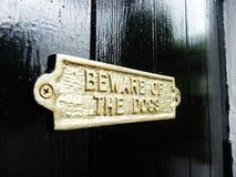 Vorsicht, bissiger Hund Zeichen auf einer schwarzen Tür golden Lizenzfreie Stockbilder
