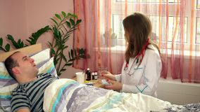 Vorsichtige Ärztinkontrollgeduldige Manntemperatur mit digitalem Thermometer stock footage