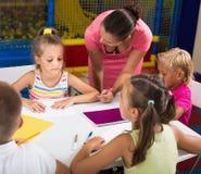 Vorsichtige Mädchen und Jungen, die Bleistifte auf Lektion zeichnen Lizenzfreie Stockfotos