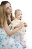 Vorsichtige Mutter kleidet die Tochter Stockbild