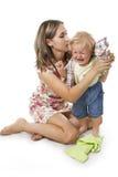 Vorsichtige Mutter kleidet die Tochter Stockfotos