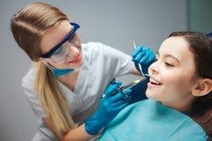 Vorsichtige weibliche Zahnarztgriffwerkzeuge nah an Mädchenmund Kindershowvorderzähne Sie sitzt ruhig im zahnmedizinischen Stuhl lizenzfreies stockbild