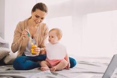 Vorsichtiger Babysitter, der ein Glas Säuglingsnahrung bei der Fütterung eines Kleinkindes hält Stockbilder