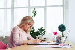 Vorsichtiger blonder trinkender Kaffee beim Schreiben Lizenzfreie Stockfotos