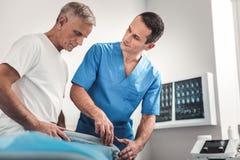 Vorsichtiger Chiropraktor, der Patienten nach seinen Schmerz fragt stockbilder