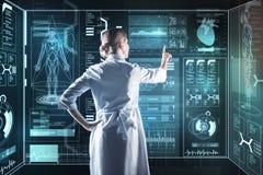 Vorsichtiger Doktor, der einen futuristischen Computer beim Arbeiten berührt stockfoto