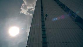Vorsichtiger männlicher Athlet, der hinunter hohes Haus und helles Sonnenlicht absteigt stock video footage