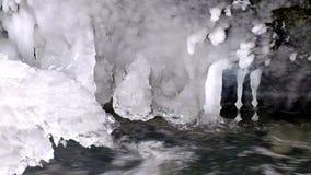 Vorst sneeuw grote kei in duidelijk koud water van bergrivier De kleine ijskegels schitteren boven kristalwater van lawaaierige s stock footage