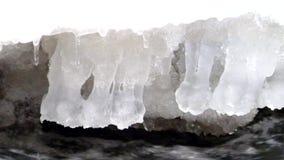 Vorst sneeuw grote kei in duidelijk koud water van bergrivier De kleine ijskegels schitteren boven kristalwater van lawaaierige s stock videobeelden