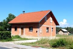 Vorstadtfamilienhaus des kleinen unfertigen Ziegelsteines mit alter hölzerner Halle im Hintergrund stockfotografie